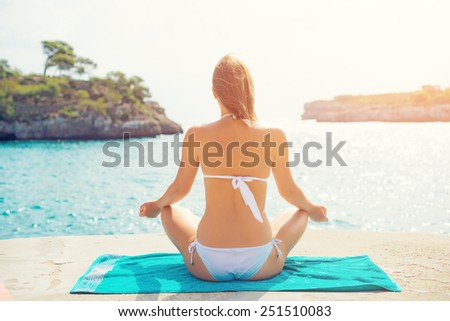 Young woman practising yoga near the sea. - stock photo
