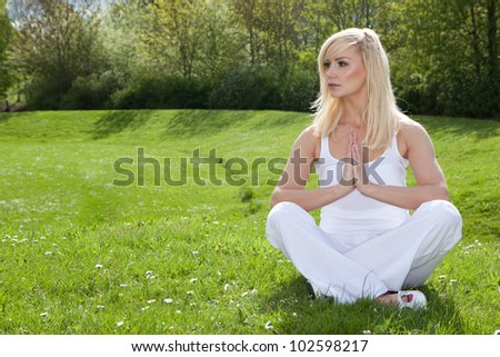 Young woman practising yoga sitting on green grass in the park as she goes through her exercise routine seeking tranquillity - stock photo