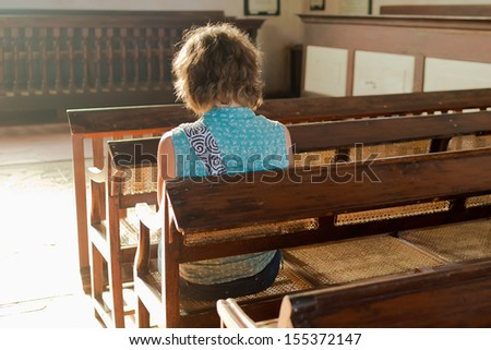 Young woman praying in a church  - stock photo