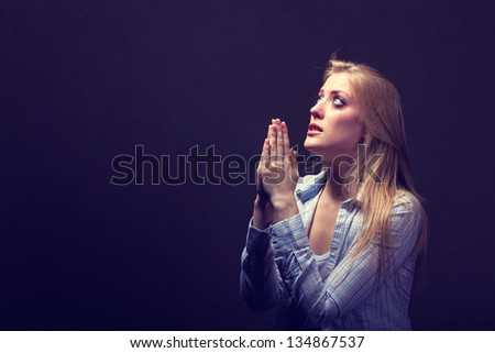 Young woman praying  on a dark background - stock photo