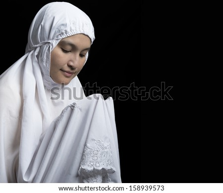 Young Woman Praying on black background - stock photo