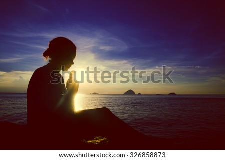 Young woman praying sunset over the Ocean Concept - stock photo