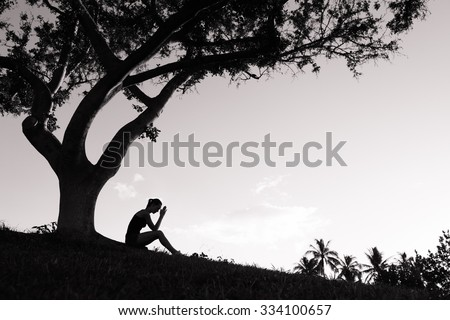 Young woman praying under a tree.  - stock photo