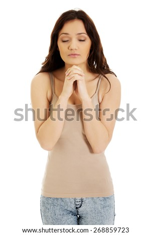 Young woman praying with her hands together and eyes closed. - stock photo