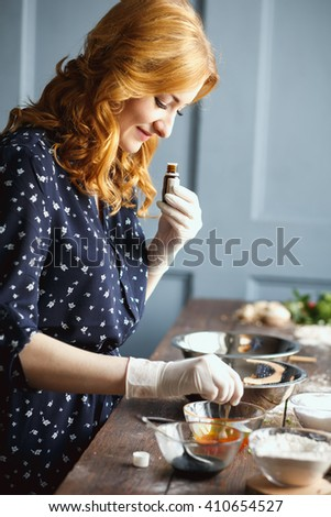 Young woman prepare bath bombs. Ingredients and floral decor on a wooden vintage table. - stock photo