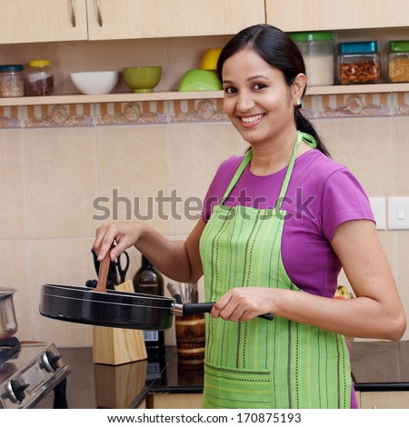 Young woman preparing a dish in her kitchen  - stock photo