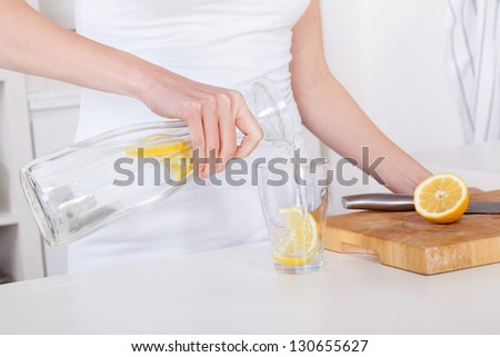 young woman preparing and drinking lemonade in her modern kitchen - stock photo