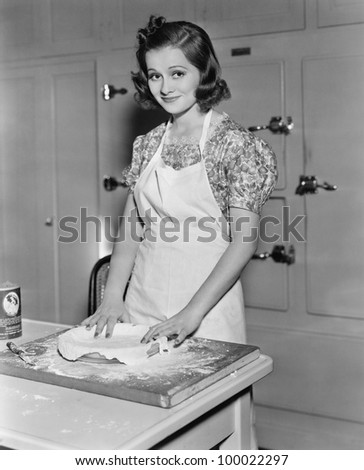 Young woman preparing food in the kitchen - stock photo