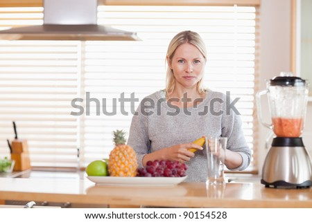 Young woman preparing fruits for the blender - stock photo