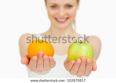 Young woman presenting fruits while smiling against white background - stock photo