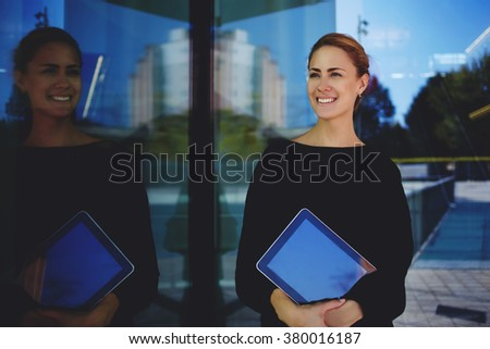Young woman professional realtor smiling for her clients which she expects outdoors near modern building, cheerful female skilled manager holding digital tablet while standing outside of big company - stock photo