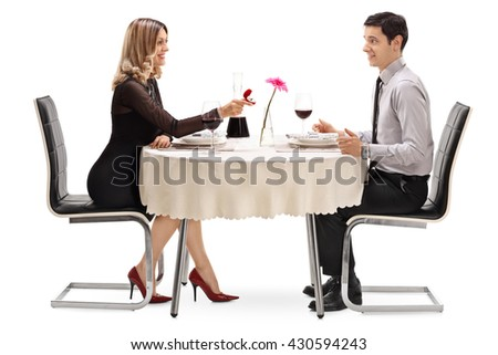 Young woman proposing to her boyfriend at a restaurant table isolated on white background - stock photo
