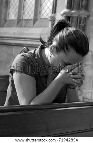 Young woman prying in the church - stock photo