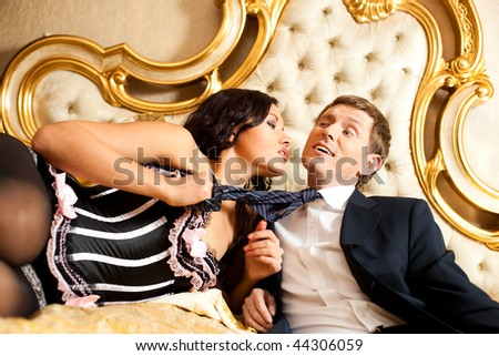 Young woman pulling man in bed. Saturated golden colors. - stock photo