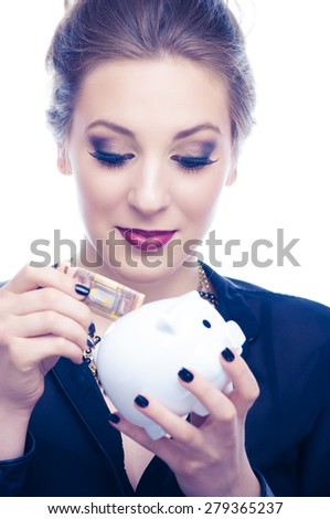 Young woman put 50 Euro banknote in a piggybank - stock photo