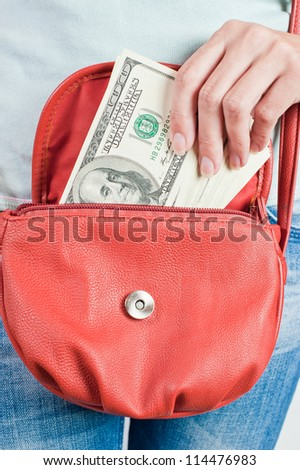 Young woman puts banknotes of U.S. dollars in a handbag - stock photo