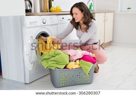 Young Woman Putting Clothes Into Washing Machine At Home - stock photo