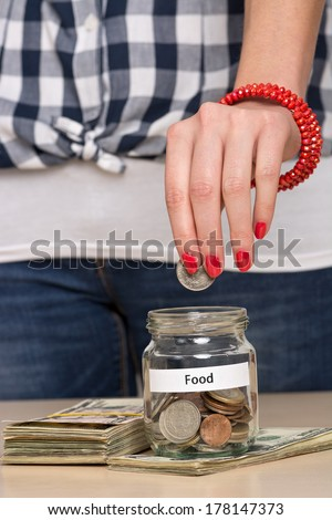 Young woman putting coin into a jar. She is saving money for daily bread. - stock photo