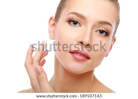 Young woman putting cream on her face Isolated on white background - stock photo