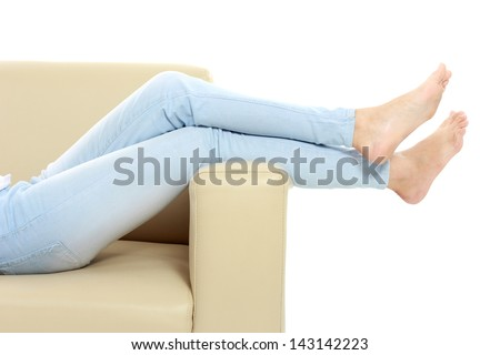 Young woman putting her feet up on sofa - stock photo