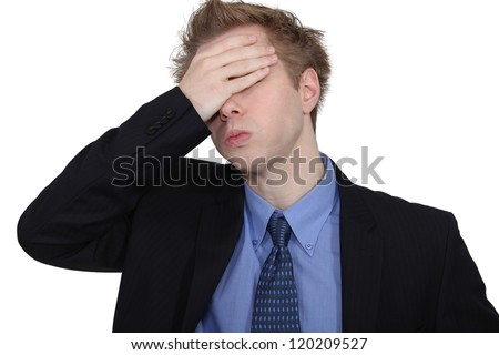 Young woman putting her hands to her head - stock photo