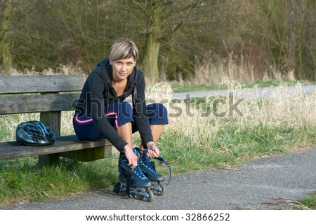 Young woman putting on rollerblades in a park. - stock photo