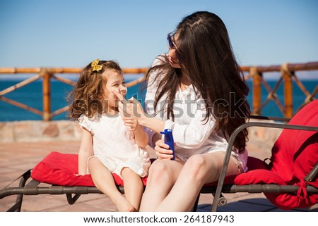 Young woman putting some sunblock on her daughter's face before going down to the beach on a sunny day - stock photo
