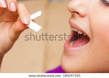 Young woman putting two chewing gum pellets in her mouth. - stock photo