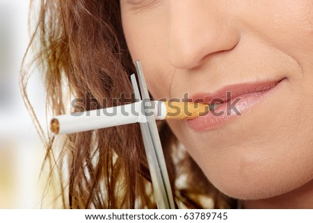 Young woman quiting smoking - focus on hand - stock photo