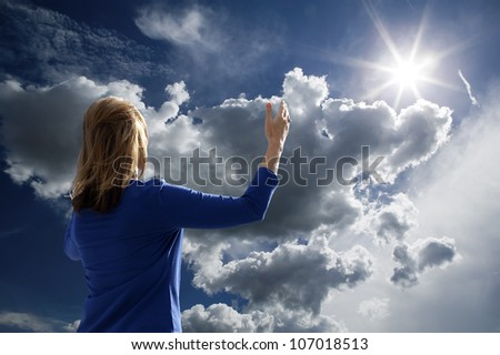 Young woman raising her arms in worship and praise while facing the late afternoon sun. - stock photo
