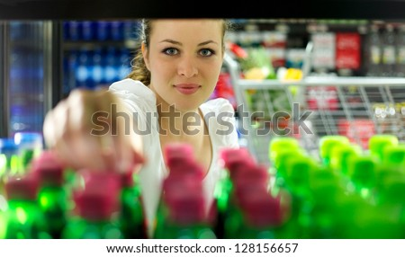 Young Woman reaching for a bottle in a Supermarket - stock photo