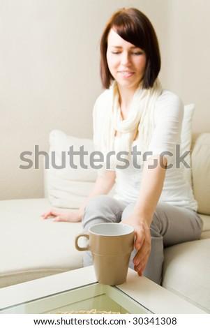 Young woman reaching for a coffee mug - stock photo
