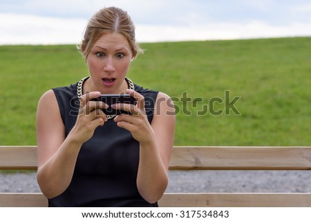 Young woman reacting in shock to an sms of text message on her mobile phone looking at the screen in wide eyed horror as she sits on a park bench outdoors - stock photo