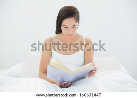Young woman reading a book in bed at home - stock photo