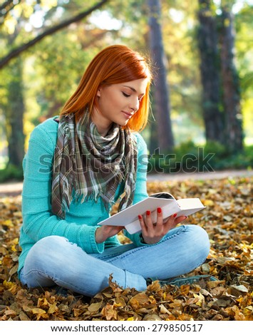 Young woman reading a book in park. - stock photo