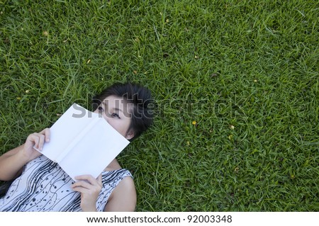 Young woman reading a book in the field - stock photo