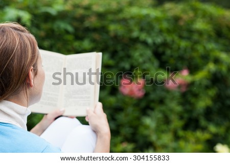 Young woman reading a book in the garden - stock photo