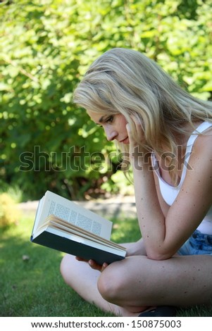 Young woman reading a book in the garden sitting sideways cross legged on the grass concentrating on the story - stock photo