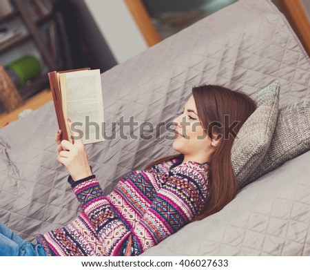 Young woman reading a book lying down in the living room - stock photo