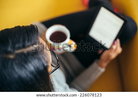 Young woman reading a book on sofa - stock photo