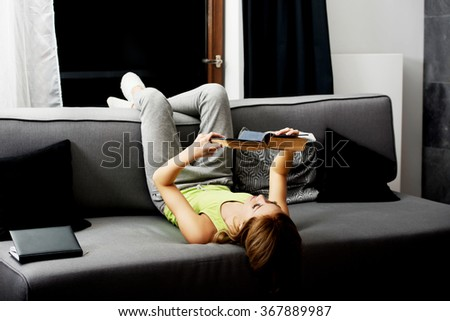 Young woman reading a book on sofa. - stock photo
