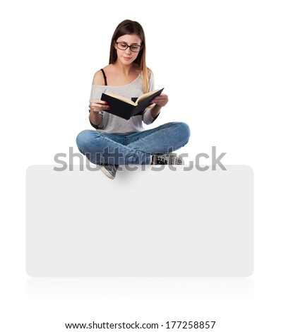 young woman reading a book sitting on a white placard - stock photo