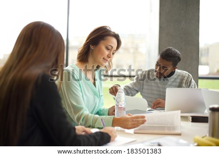 Young woman reading a book with other students studying around. Young university students studying at library. - stock photo