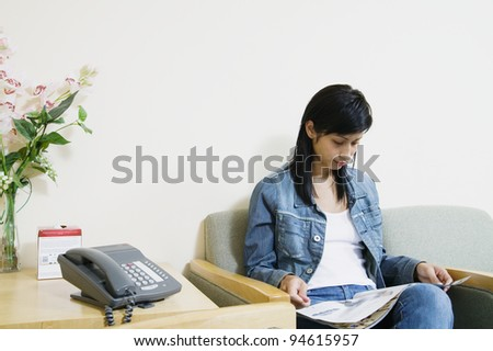Young woman reading a magazine waiting in a waiting room - stock photo