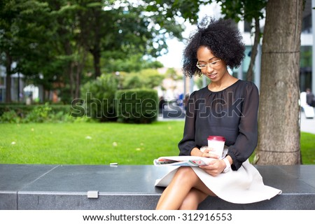 young woman reading a magazine with a coffee - stock photo