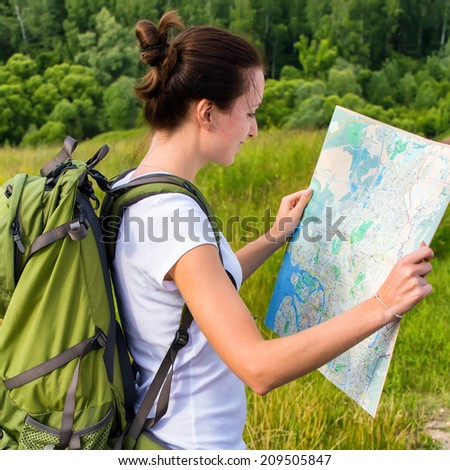 Young woman reading a map on a hiking trip - stock photo