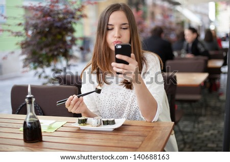 Young woman reading a message while eating sushi in a restaurant - stock photo