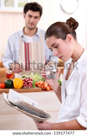 Young woman reading a newspaper while her boyfriend prepares lunch - stock photo