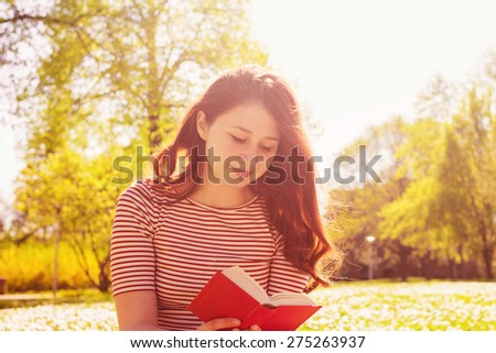 Young woman reading book in a city park.Student young girl reading a book in a city park. - stock photo