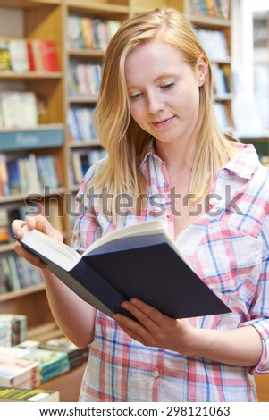 Young Woman Reading Book In Bookstore - stock photo